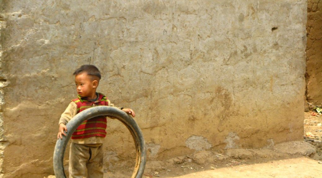 rural china play, Nosy boy playing with tire
