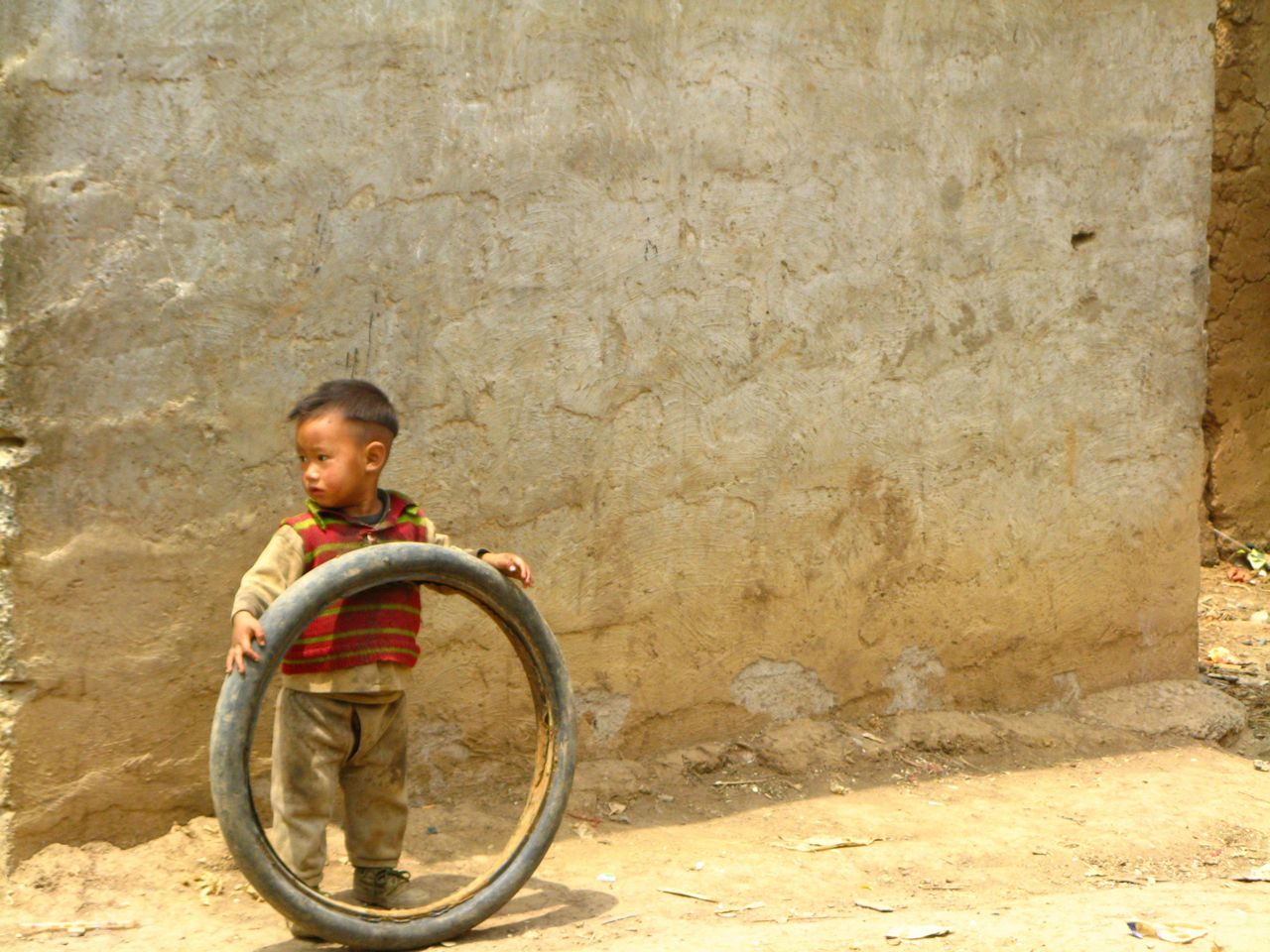 Rural china play nosy boy playing with tire